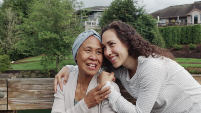 mixed race senior woman sitting with her adult daughter outdoors - hawaiian ethnicity stock videos & royalty-free footage