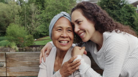 mixed race senior woman sitting with her adult daughter outdoors - pacific islander stock videos & royalty-free footage