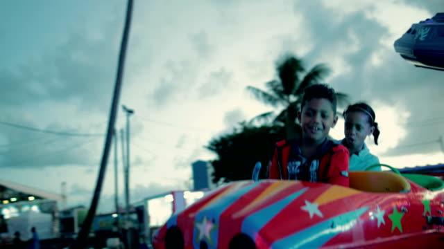 stockvideo's en b-roll-footage met mixed race sibling couple on a children's carousel in the caribbean - franse overzeese gebieden