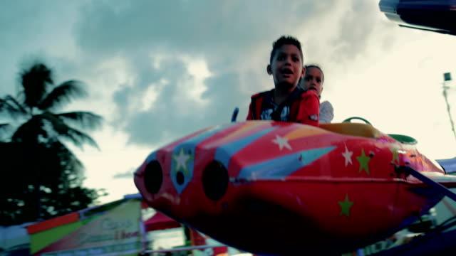 vídeos de stock, filmes e b-roll de mixed race sibling couple on a children's carousel in the caribbean - territórios ultramarinos franceses