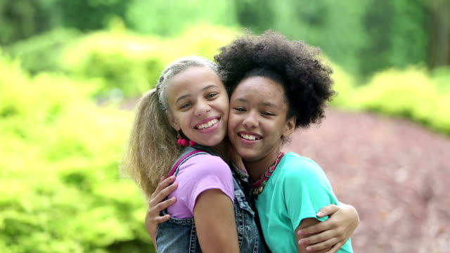 mixed race sisters, giggling, hugging - side by side stock videos & royalty-free footage