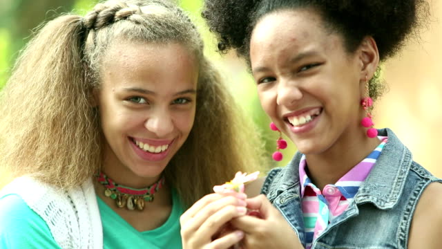 vídeos de stock e filmes b-roll de mixed race sisters outdoors, holding flower, smiling - 14 15 years