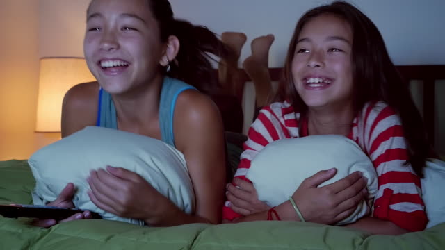 mixed race sisters watching television on bed - teenage girl watching tv stock videos & royalty-free footage