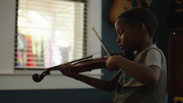 vídeos de stock e filmes b-roll de mixed race son - violino