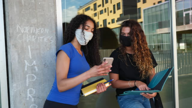 mixed race students interacting on campus while wearing protective face masks - back to school stock videos & royalty-free footage