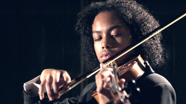 Mixed race teenage boy playing violin