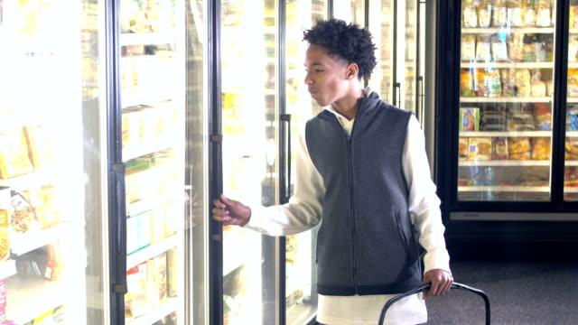 mixed race teenage boy shopping for groceries - un ragazzo adolescente video stock e b–roll