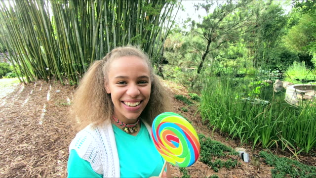mixed race teenage girl at park with lollipop - only teenage girls stock videos and b-roll footage