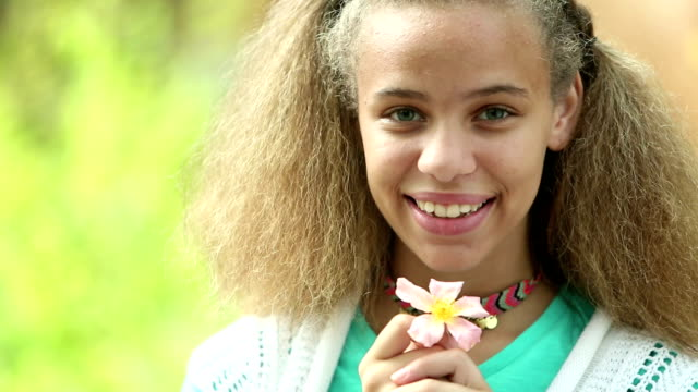 mixed race teenage girl outdoors holding flower - frizzy hair stock videos and b-roll footage