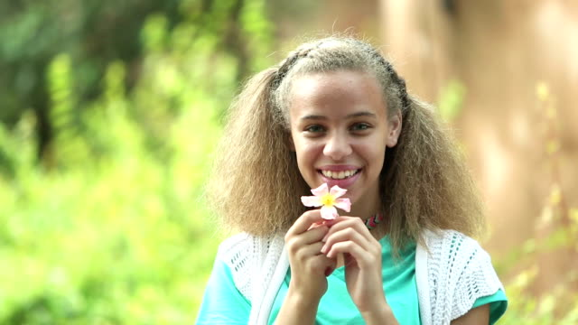 mixed race teenage girl outdoors holding flower - only teenage girls stock videos & royalty-free footage