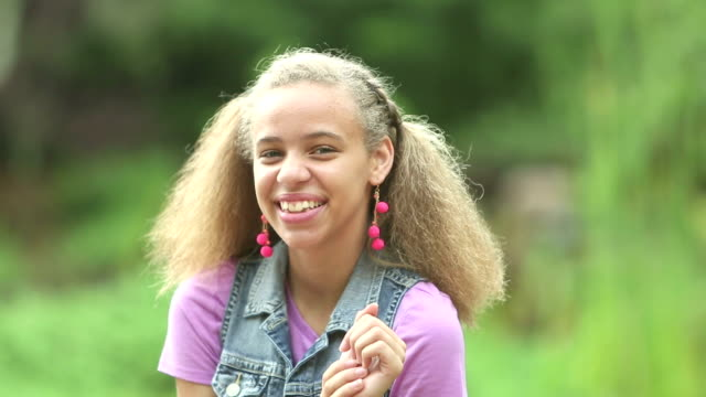 mixed race teenage girl outdoors, smiling at camera - only teenage girls stock videos & royalty-free footage