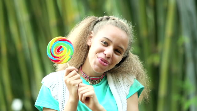 mixed race teenage girl peeking out from behind lollipop - only teenage girls stock videos and b-roll footage