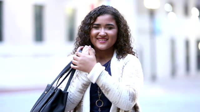 mixed race teenager walking in city - shoulder bag stock videos & royalty-free footage