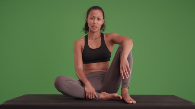 Mixed race woman athlete sitting down on matt looking at camera on green screen
