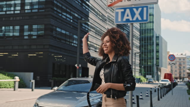 mixed race woman catching an uber in the city center. using mobile app - taxi stock videos & royalty-free footage
