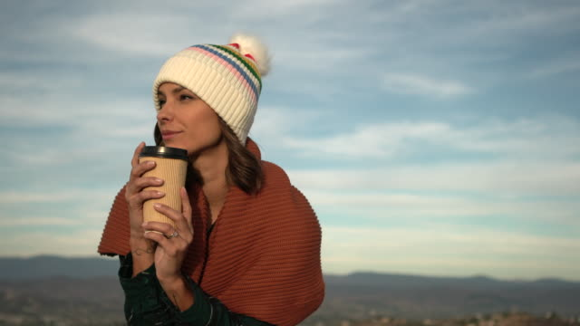 vidéos et rushes de ms mixed race woman drinking coffee in a knit hat - boisson chaude
