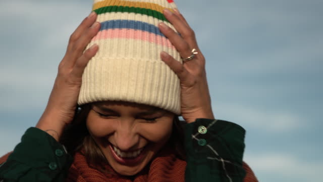 cu mixed race woman in a knitted beanie smiling - cappello video stock e b–roll