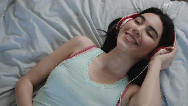 Mixed Race woman listening to music on headphones