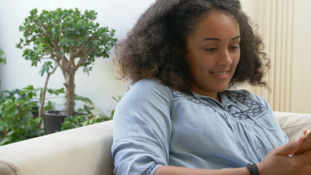 Mixed race woman sits on sofa looking at her mobile phone.