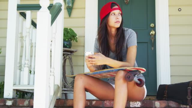 vídeos y material grabado en eventos de stock de mixed race woman sitting on porch with skateboard texting - incertidumbre