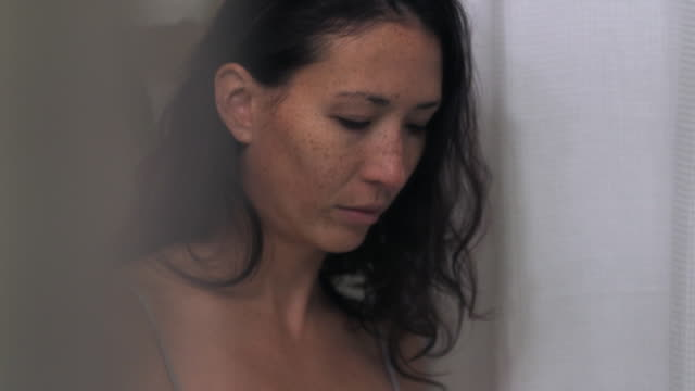 mixed race woman washing face in bathroom mirror - routine stock-videos und b-roll-filmmaterial