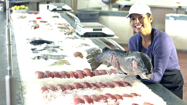 mixed race woman working in seafood market with big fish - fish market stock videos and b-roll footage