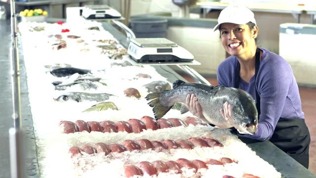 Blandad ras kvinna som arbetar på fiskmarknaden med stor fisk