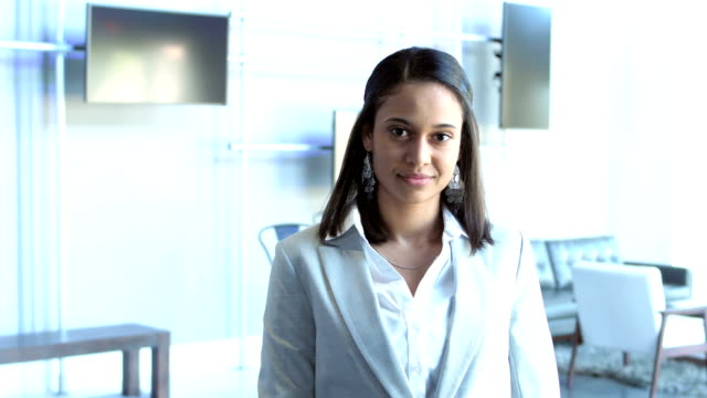 mixed race young businesswoman in business lounge - trade show stock videos & royalty-free footage
