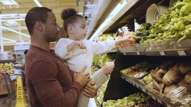mixed race young family shopping for vegetables - fare spese video stock e b–roll