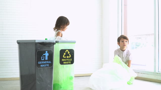 mixed raced austrian thai boys and english thai girl learning, helping to separate plastic bottles into the recyclable bin. boy finding waste in the green waste bag. concept of teaching sustainable leisure activity of caucasian children in the home. - ease stock videos & royalty-free footage