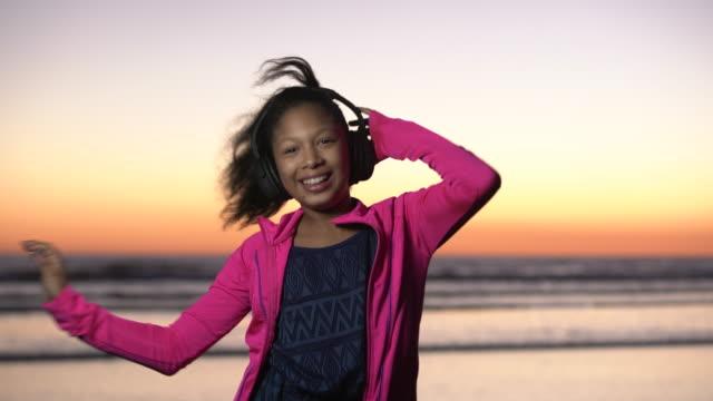vídeos de stock, filmes e b-roll de ms mixed raced girl dancing on the beach at sunset - 10 11 anos