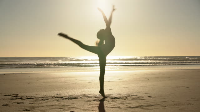 ws mixed raced girl dancing on the beach at sunset - haar nach hinten stock-videos und b-roll-filmmaterial
