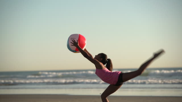 ms mixed raced girl playing with a ball on the beach at sunset - ビーチボール点の映像素材/bロール