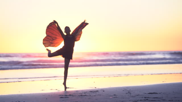 ms mixed raced girl wearing butterfly wings dancing on the beach at sunset - farfalla video stock e b–roll