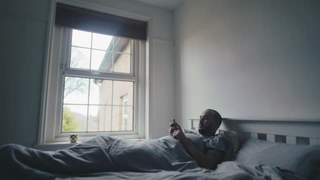 Mixed raced man getting up out of bed