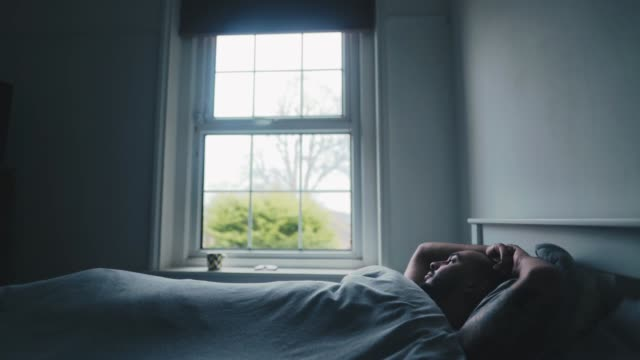 Mixed raced man laying in bed staring outside a window