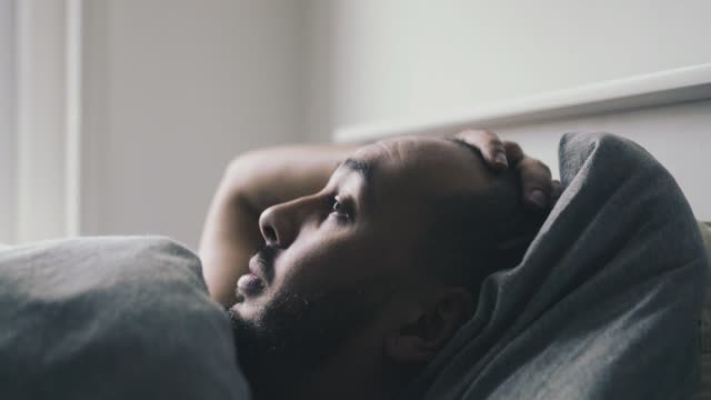 Mixed raced man waking up out of bed