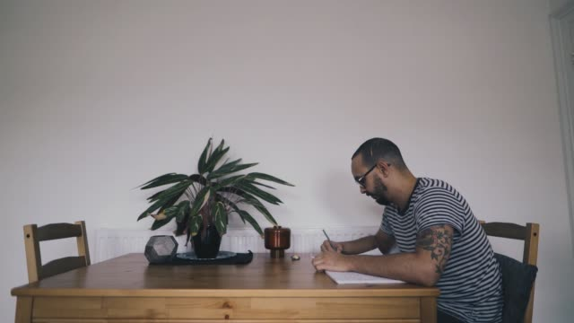 mixed raced man writing in notebook - modern manhood stock videos & royalty-free footage