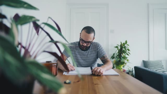 Mixed raced man writing in notebook