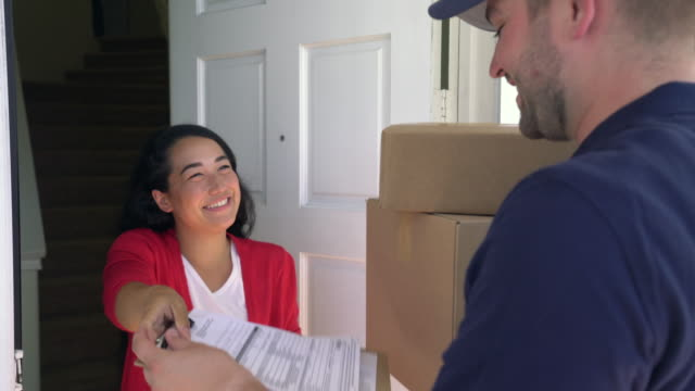 ms mixed raced person receiving packages from a delivery man. - doorway stock videos and b-roll footage