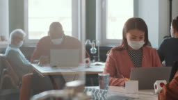 Mixed Raced Woman in Face Mask Working on Laptop in Office
