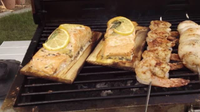 vídeos de stock e filmes b-roll de mixed seafood grill with salmon, scallops and jumbo shrimp - filete de salmão