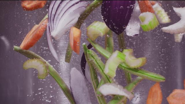 vídeos y material grabado en eventos de stock de vegetales mezclados como zanahorias, cebollas, frijoles verdes, papas cayendo en agua hirviendo super slow motion 1000 fps - hervido