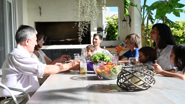 mixed-age range hispanic family eating lunch outdoors - argentina stock videos & royalty-free footage