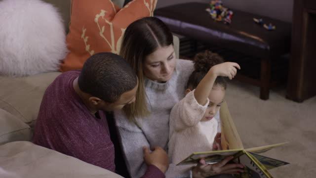 Couple de Race mixte lecture à leur jeune fille