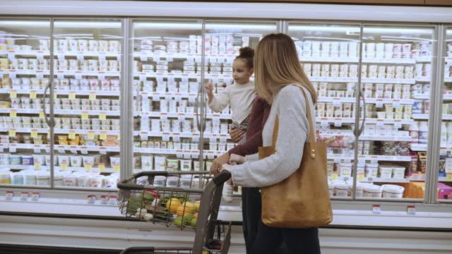 乳製品のセクションを通して食料品のカートを押す混血家族 - 食料品点の映像素材/bロール