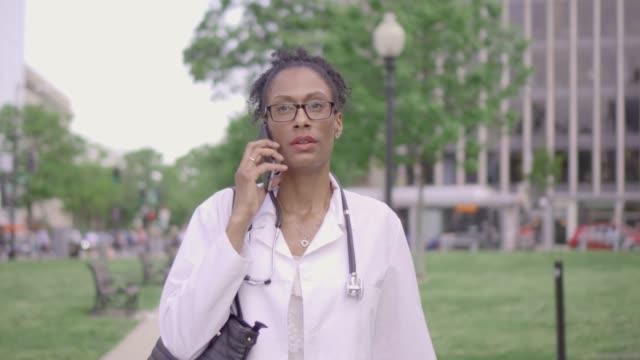vídeos de stock, filmes e b-roll de raça mista femininas médicas profissionais conversações sobre telefone - só uma mulher madura