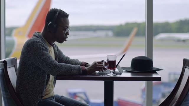 mixed-race millennial man listens to music while he works on tablet at window in airport terminal. - business travel stock videos & royalty-free footage