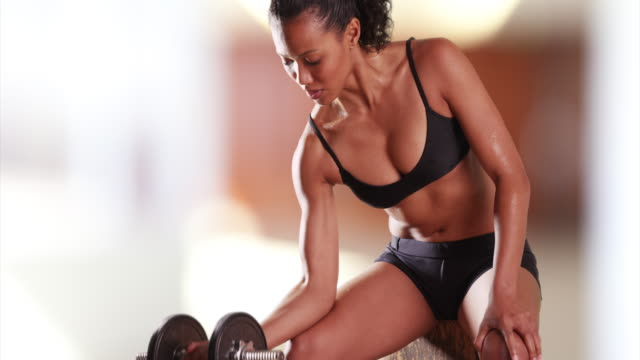 mixed-race millennial woman lifting weights at the gym - arm curl stock videos and b-roll footage