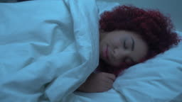 Mixed-race woman sleeping in bed, covered with blanket, orthopedic mattress